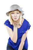 Beautiful blonde woman in casual attire with hat blowing a kiss — Stock Photo