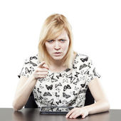 Blonde woman in business attire at desk pointing — Stock Photo