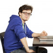 Student sitting at table using computer — Stock Photo