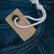 Retro cardboard paper tag with string in denim jeans pocket — Stock Photo