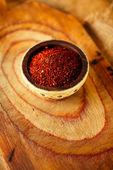 красный горячий перец перец хлопьев в чашу на деревянную доску backgro — Стоковое фото