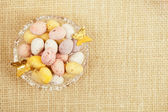 Easter chocolate speckled eggs in bowl on hessian table — Stock Photo