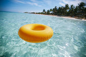 Floating ring on blue clear sea with beach, shallow dof — Stockfoto
