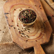 Mixed pepper, pink, black, white, green in bowl  on  wooden boar - Stock Photo