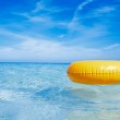 Floating yellow ring on crystal blue sea water with sky, shallow — Stock Photo #18537423