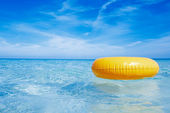 Floating yellow ring on crystal blue sea water with sky, shallow — Stock Photo