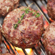 Burgers on bbq  barbecue grill with fire - Stock Photo
