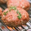 Stock Photo: Raw burgers on bbq barbecue grill with fire