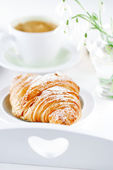 Croissant with coffee, on sunlit breakfast tray — Stock Photo