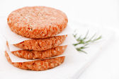 Raw burgers for hamburgers, in a pile — Stock Photo