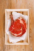 Bone-in Rib eye Steak steak on paper and wooden table — Stock Photo