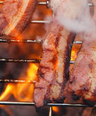 Bacon meat on bbq barbecue grill with fire — Stock Photo