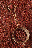 Fine grated chocolate 100 percent dark in sieve , backdrop, background — Stock Photo