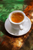 Espresso coffee cup on rustic table with sun — Stock Photo