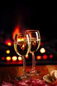 Dois copos de vinho brancos com fundo aconchegante lareira — Foto Stock