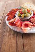 Platter of serrano jamon Cured Meat, Ciabatta, chorizo and olive — Stock Photo