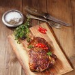 Beef steak with red chillies on wood and table — Stock Photo