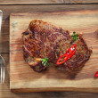 Beef steak with red chillies on wood and table — Stock Photo #28367275