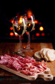 Platter of serrano jamon Cured Meat with cozy fireplace and wine — Stock Photo