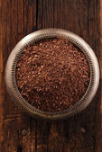 Fine grated chocolate in bowl on wood , shallow dof — Stock Photo