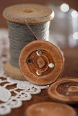 Real old reels spoons treads with needle and thimble on old wood — Stock Photo