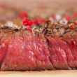 Beef steak on a wooden board and table — Stock Photo #33009925