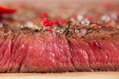 Beef steak on a wooden board and table — Stock Photo