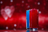 Slush ice in glasses, red and blue on glitter star background — Stock Photo