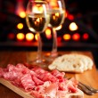 Platter of serrano jamon Cured Meat with cozy fireplace and wine — Stock Photo #33831865