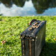 Old black suitcase by the river  — Stock Photo