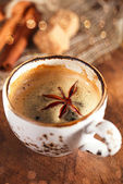 A cup of spiced coffee with anis star and cinamon sticks and sug — Stock Photo