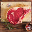 Raw beef Rib bone  steak   on wooden board and table — Stok fotoğraf