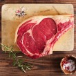 Raw beef Rib bone  steak   on wooden board and table — Стоковая фотография