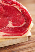 Raw beef Rib steak with bone on wooden board and table — Stock Photo