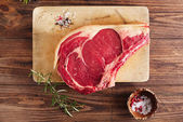 Raw beef Rib bone steak on wooden board and table — Zdjęcie stockowe