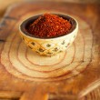 Red hot chillies pepper flakes in bowl on wooden board backgro — Stock Photo