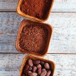 Stock Photo: Cocobeans, powder and grated chocolate in wooden bowls, white