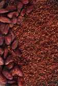 Cocoa beans and grated chocolate background on black — Stock Photo