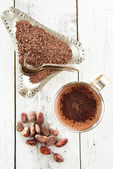 Hot chocolate, cocoa beans and grated chocolate on white wooden — Stock Photo