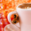 Festive cup of hot drink with cinnamon sticks and golden red gl — Stock Photo #37556497