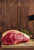Raw beef Rib bone steak on wooden board and table — Stock Photo