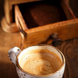 A cup of espresso coffee with Old coffee mill textured table — Stock Photo