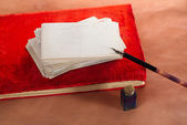 Pile of vintage post cards on red album with  ink pen, inkpot — Stock Photo