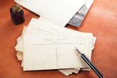 Pile of vintage post cards with  ink pen, inkpot — Stock Photo