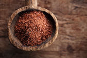 Fine grated chocolate in old wooden spoon — Stock Photo