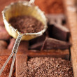 Hot chocolate flakes  in old rustic style silver sieve on wooden — Stock Photo #48895215