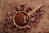 Cocoa powder in spoon on roasted cocoa chocolate beans backgroun — Stock Photo