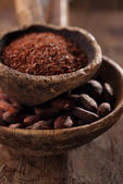 Cocoa beans and grated dark chocolate in old texured spoons bowl — Stock Photo