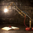 Light from a gas burner at the table next to the black book and — Stock Photo #20474763