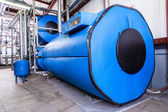 Big blue reservoirs in factory boiler room — Stock Photo
